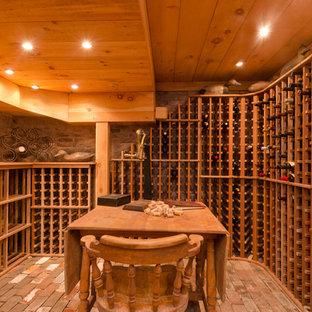 Bild på en mycket stor vintage vinkällare, med tegelgolv och vinhyllor