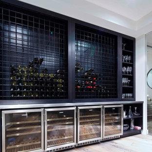 Exempel på en modern vinkällare, med vinhyllor och grått golv