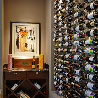 Idées déco pour une petit cave à vin classique avec béton au sol et des casiers.