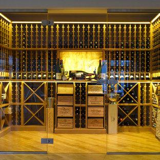 Réalisation d'une grand cave à vin design avec des casiers, un sol en bois clair et un sol marron.