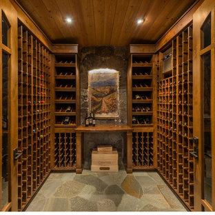 Imagen de bodega de estilo americano, grande, con suelo de pizarra y botelleros