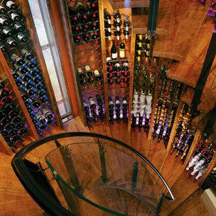 Idée de décoration pour une cave à vin bohème avec un sol en bois brun et des casiers.