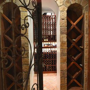 Exempel på en mellanstor shabby chic-inspirerad vinkällare, med klinkergolv i terrakotta, vindisplay och orange golv