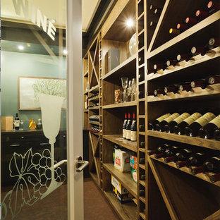 Cette photo montre une grand cave à vin chic avec un sol en liège, un présentoir et un sol marron.