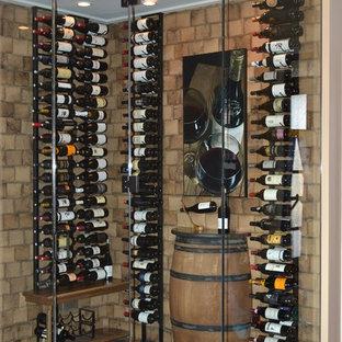Cette photo montre une cave à vin tendance avec un sol en bois brun, un présentoir et un sol multicolore.