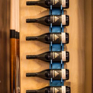 Ejemplo de bodega actual, pequeña, con moqueta, botelleros y suelo gris