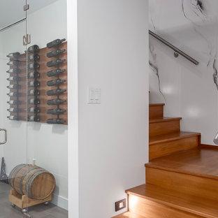 Esempio di una piccola cantina design con pavimento in legno massello medio, portabottiglie a vista e pavimento grigio