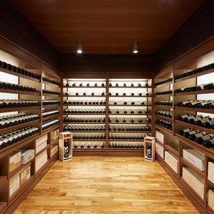 Diseño de bodega clásica renovada con suelo de madera en tonos medios, vitrinas expositoras y suelo naranja