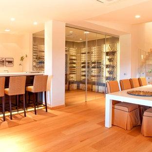 Immagine di una grande cantina design con portabottiglie a vista, parquet chiaro e pavimento marrone