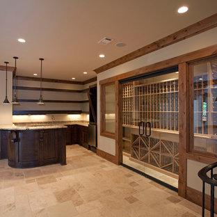 Cette image montre une cave à vin chalet de taille moyenne avec un sol en travertin, des casiers et un sol beige.