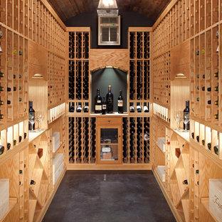 Bild på en mellanstor vintage vinkällare, med betonggolv, vinhyllor och svart golv