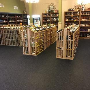 Immagine di una grande cantina con rastrelliere portabottiglie e pavimento nero
