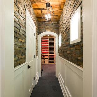 Idée de décoration pour une cave à vin chalet de taille moyenne avec un sol en ardoise, des casiers et un sol noir.