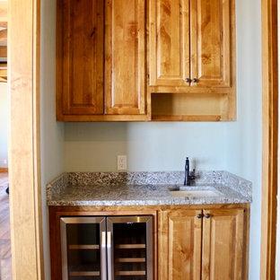 Inspiration pour une grand cave à vin rustique avec un sol en bois brun, un présentoir et un sol vert.