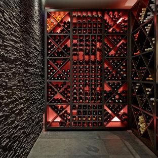 Aménagement d'une petit cave à vin contemporaine avec un sol en ardoise et des casiers.