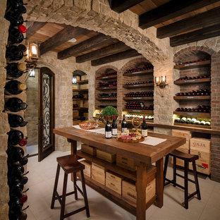 На фото: винный погреб среднего размера в средиземноморском стиле с стеллажами и полом из керамогранита с