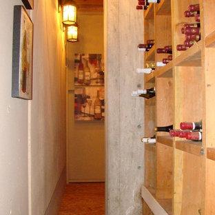 Cette photo montre une petit cave à vin méditerranéenne avec un sol en contreplaqué, un présentoir et un sol marron.