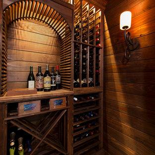 Idée de décoration pour une petit cave à vin chalet avec un sol en travertin, des casiers losange et un sol beige.