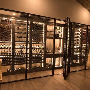 Inspiration för stora moderna vinkällare, med mellanmörkt trägolv, vindisplay och brunt golv
