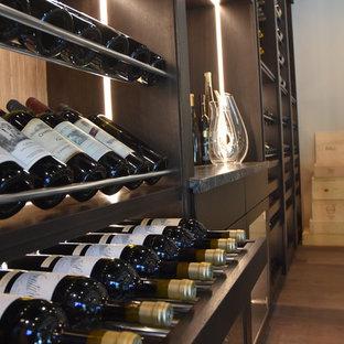 Aménagement d'une grand cave à vin contemporaine avec un sol en bois brun, un présentoir et un sol marron.