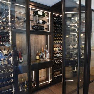 Источник вдохновения для домашнего уюта: большой винный погреб в современном стиле с паркетным полом среднего тона, витринами и коричневым полом