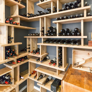 Ejemplo de bodega minimalista, pequeña, con suelo de madera en tonos medios, botelleros y suelo gris