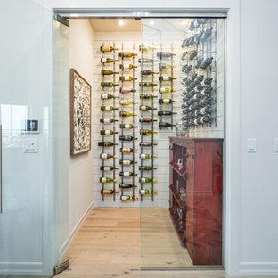 Foto på en mellanstor lantlig vinkällare, med ljust trägolv, vinhyllor och beiget golv