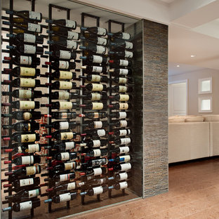 Large contemporary wine cellar in Toronto with cork flooring, display racks and beige floors.