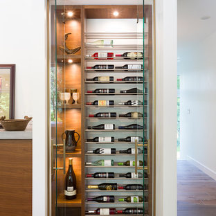 Inspiration for a small midcentury wine cellar in Other with light hardwood floors and storage racks.