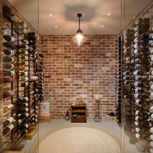Photo of a transitional wine cellar in Perth with display racks and grey floor.