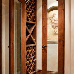 Inspiration pour une petit cave à vin méditerranéenne avec un sol en carreau de terre cuite, des casiers et un sol marron.