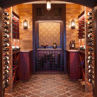 サンディエゴの大きい地中海スタイルのおしゃれなワインセラー (テラコッタタイルの床、ディスプレイラック、赤い床) の写真