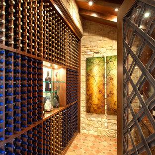 Photo of a mediterranean wine cellar in Austin with storage racks and orange floors.
