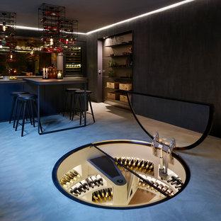 Exempel på en mellanstor modern vinkällare, med betonggolv och vinhyllor