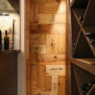 Inredning av en modern mellanstor vinkällare, med vinställ med diagonal vinförvaring, klinkergolv i porslin och grått golv
