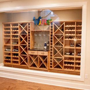 Modelo de bodega clásica renovada, grande, con suelo de madera en tonos medios, botelleros y suelo marrón