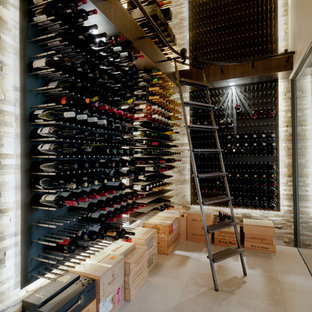 Wine cellar - contemporary limestone floor wine cellar idea in Kent with storage racks