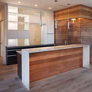 Ejemplo de bodega actual, de tamaño medio, con vitrinas expositoras, suelo marrón y suelo de madera en tonos medios