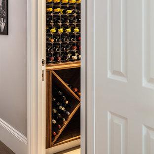 Inspiration för små klassiska vinkällare, med mellanmörkt trägolv och vindisplay