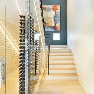 Idée de décoration pour une grand cave à vin design avec un sol en bois clair, un présentoir et un sol marron.