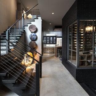 Foto di una cantina minimal di medie dimensioni con pavimento in cemento e portabottiglie a vista