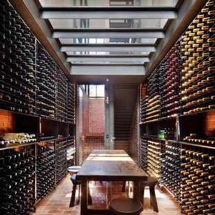 Photo of a contemporary wine cellar in Melbourne with brick floors and storage racks.