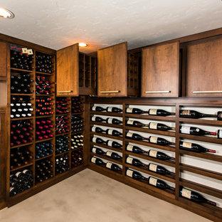 Exemple d'une cave à vin chic de taille moyenne avec béton au sol, des casiers et un sol beige.