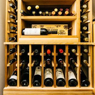 Imagen de bodega clásica renovada, de tamaño medio, con botelleros, suelo de madera en tonos medios y suelo marrón
