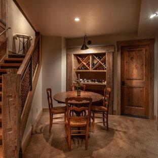 Aménagement d'une grand cave à vin montagne avec moquette, des casiers losange et un sol marron.