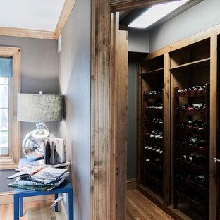 Idee per una cantina eclettica di medie dimensioni con pavimento in legno massello medio, rastrelliere portabottiglie e pavimento marrone