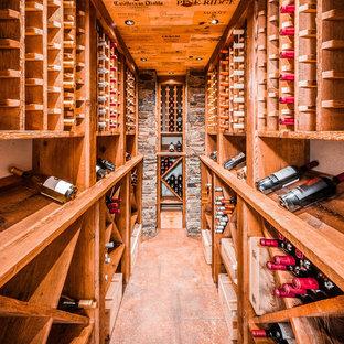 Idée de décoration pour une cave à vin marine avec des casiers et un sol marron.