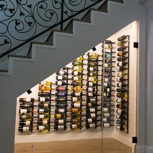 Réalisation d'une petit cave à vin tradition avec sol en stratifié, des casiers et un sol marron.