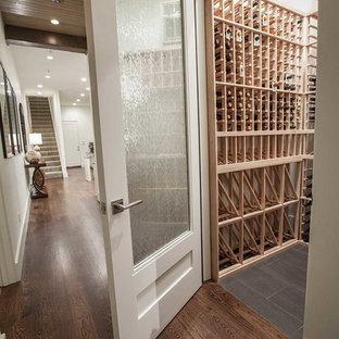 Idéer för att renovera en liten vintage vinkällare, med vinhyllor, klinkergolv i porslin och svart golv