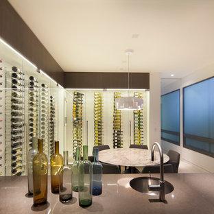 Modern inredning av en mellanstor vinkällare, med kalkstensgolv och vinhyllor